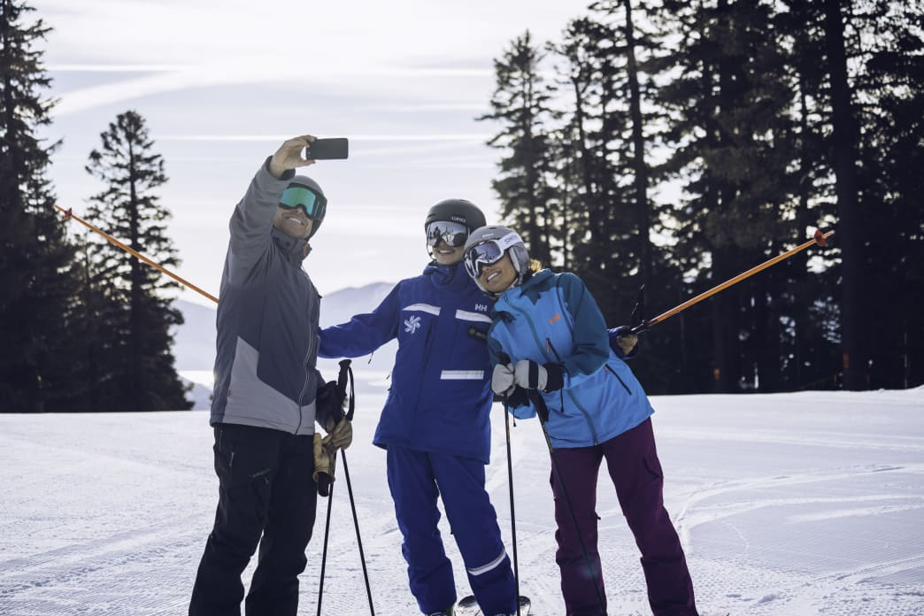 Snowboarders taking selfie with friends
